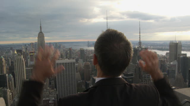 vídeos de stock, filmes e b-roll de cu rear view of businessman cheering and looking at new york cityscape / new york, usa - 30 34 anos