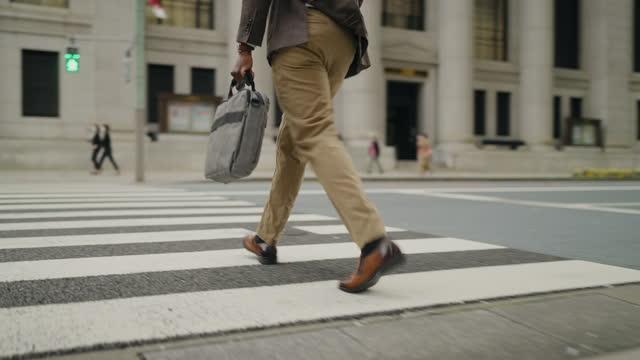 rear view of businessman crossing street - crossing stock videos & royalty-free footage