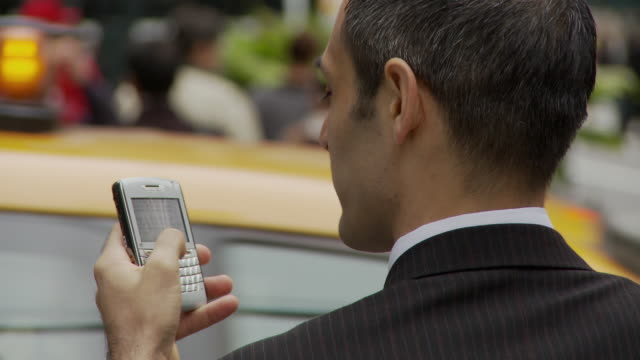 CU Rear view of businessman holding smart phone on busy street / New York City, New York, USA