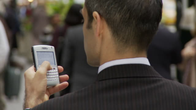 CU FOCUSING Rear view of businessman holding smart phone on busy street / New York City, New York, USA