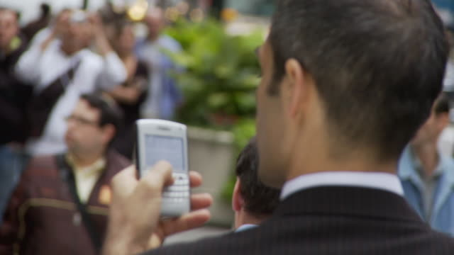 CU PAN Rear view of businessman holding smart phone on busy street / New York City, New York, USA