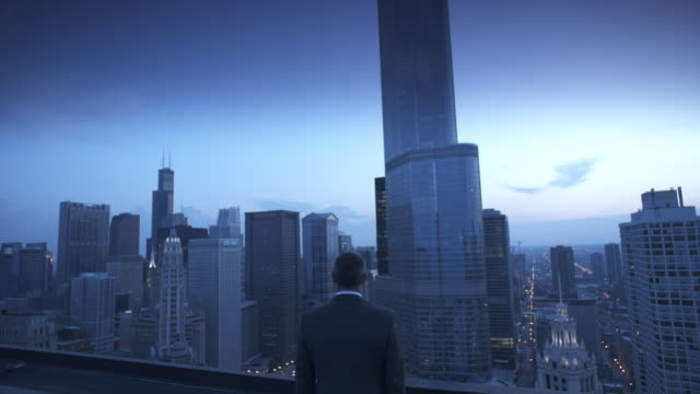 vidéos et rushes de ms zi cu rear view of businessman on roof at twilight, skyscrapers in background, chicago, illinois, usa - costume