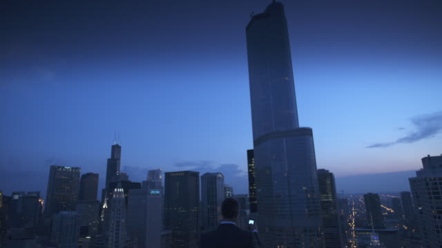 WS ZI CU Rear view of businessman using mobile phone on roof at twilight, skyscrapers in background, Chicago, Illinois, USA