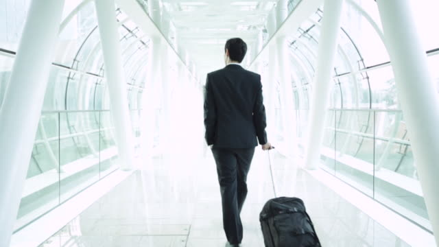 WS rear view of businessman walking through modern airport.