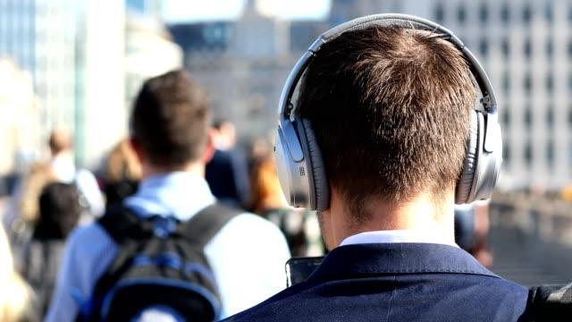Rear View Of Businessman Wearing Wireless Headphones Walking To Work In Slow Motion