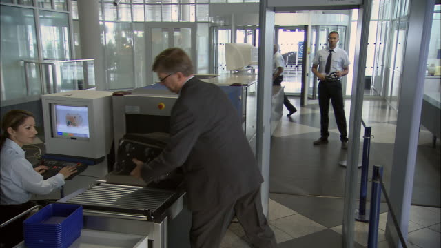 ms rear view of businesspeople going through metal detector at airport security checkpoint/ munich, germany - metal detector sicurezza video stock e b–roll