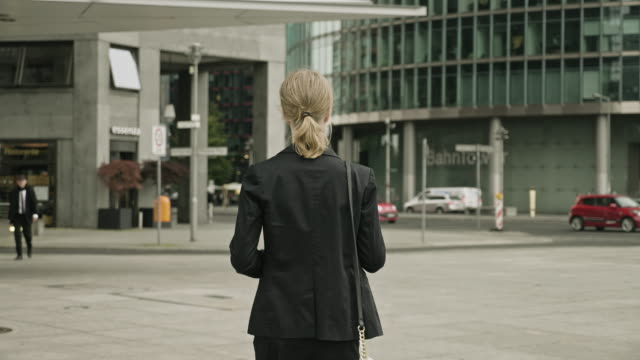 rear view of businesswoman leaving work at dusk - professione video stock e b–roll