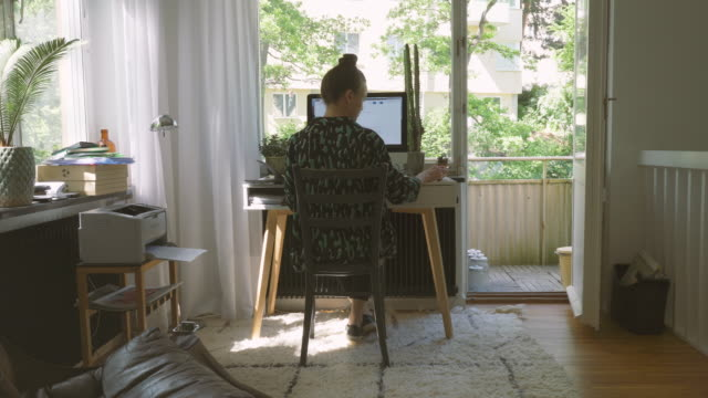 rear view of businesswoman picking up the phone at home office - sitta bildbanksvideor och videomaterial från bakom kulisserna