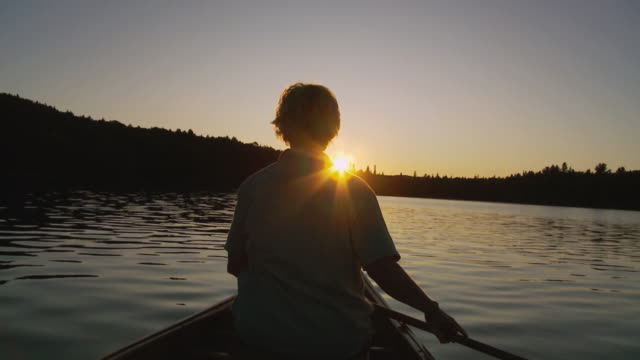 vídeos de stock, filmes e b-roll de slo mo ms rear view of canoeist on lake opeongo at sunset, algonquin park / whitney, ontario, canada - canoagem