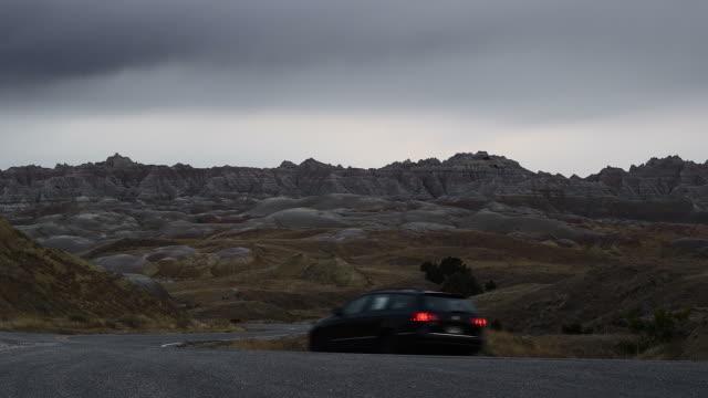 vidéos et rushes de ws, rear view of car driving through badlands national park, south dakota, usa - parc national des badlands