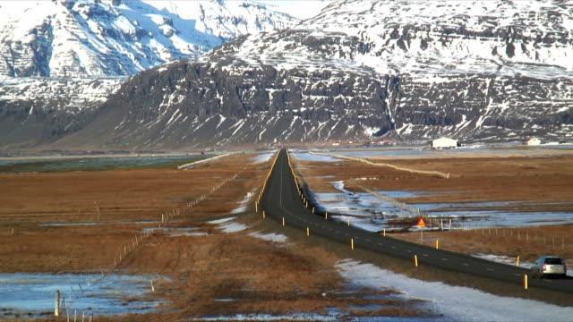 vídeos de stock, filmes e b-roll de ws zi rear view of car on icelandic ring road near jokulsarlon, snow capped mountains in background, iceland - peter snow