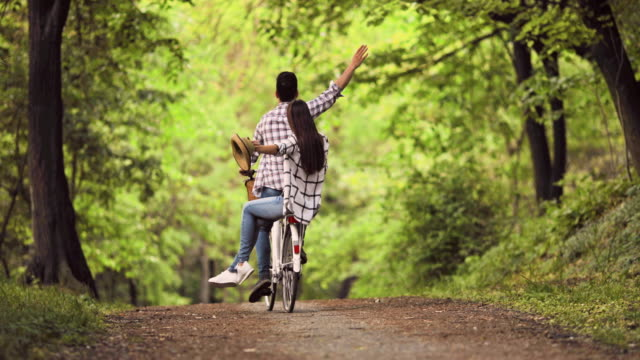 Rear view of carefree couple cycling through the forest.