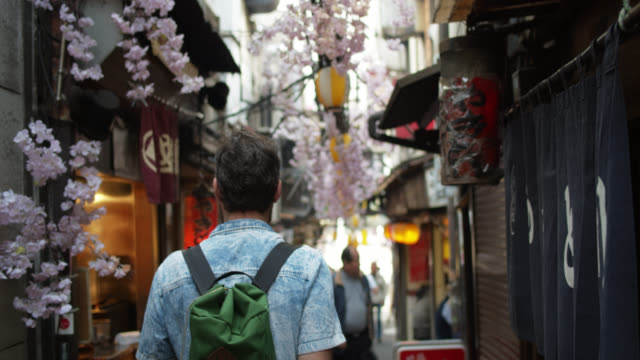 rear view of caucasian male tourist walking down smoky alley in tokyo - tourist stock videos & royalty-free footage