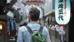 Rear View of Caucasian Tourist Walking Down Alley in Tokyo