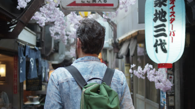 rear view of caucasian tourist walking down alley in tokyo - top capo di vestiario video stock e b–roll