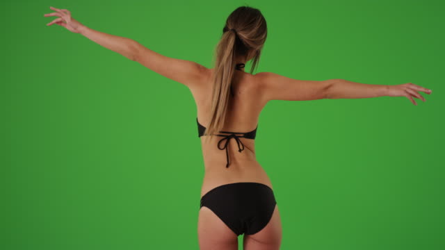Rear view of Caucasian woman in swimsuit with arms outstretched on greenscreen