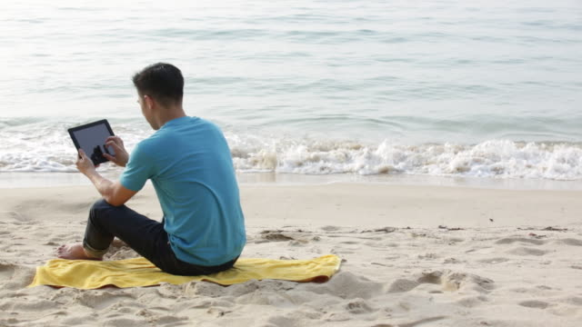 vídeos de stock, filmes e b-roll de ws rear view of chinese man sitting on the beach with a digital tablet.  - toalha de praia