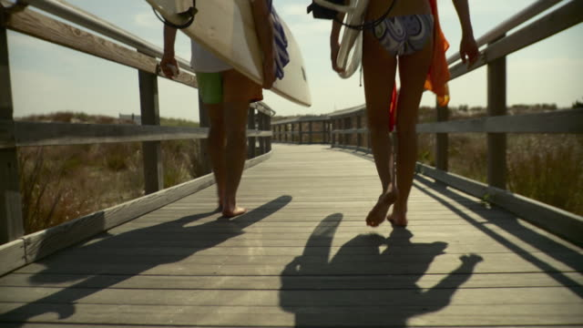 ms tu td rear view of couple carrying surfboards, walking down boardwalk towards beach / long beach, new york state, usa - long island video stock e b–roll