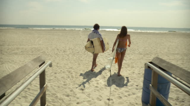 ws rear view of couple carrying surfboards, walking on beach / long beach, new york state, usa - long island video stock e b–roll