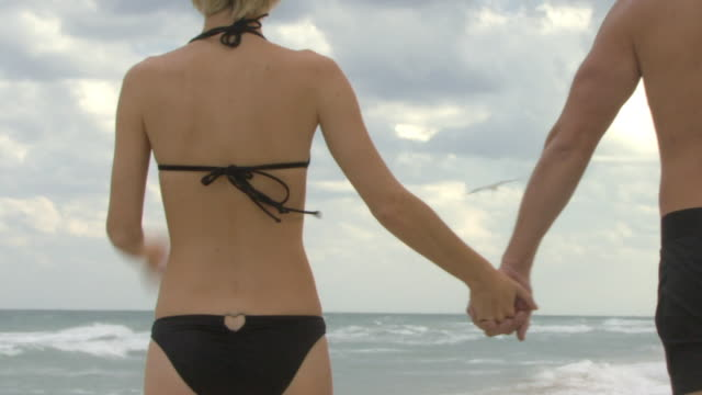 cu ws rear view of couple holding hands walking on beach / miami, florida, usa - swimming shorts stock videos & royalty-free footage