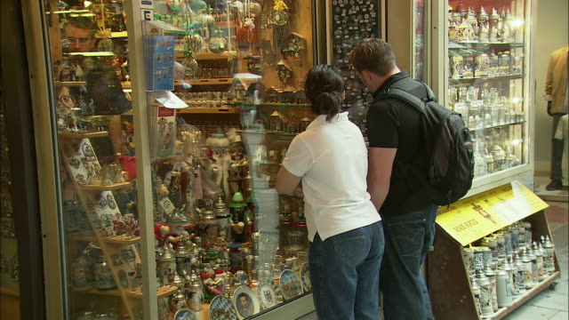 ms rear view of couple looking at gift shop display, marienplatz, munich, bavaria, germany - zaino da montagna video stock e b–roll