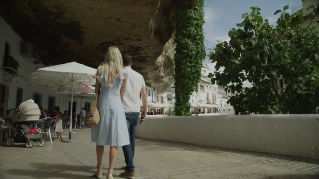 rear view of couple photographing rock overhang with cell phone / setenil de las bodegas, malaga, spain - cádiz stock videos and b-roll footage
