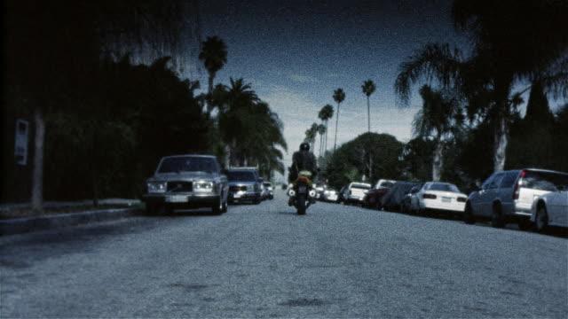 vidéos et rushes de rear view of couple riding motorcycle down street away from locked down camera - procédé croisé