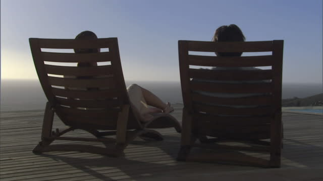 vidéos et rushes de ms rear view of couple sitting in lounge chairs on deck overlooking the ocean and holding hands/ cape town, south africa - siège de jardin ou de plage