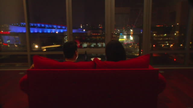 vidéos et rushes de ms, cs, rear view of couple sitting on couch facing window at night, los angeles, california, usa - vue de dos