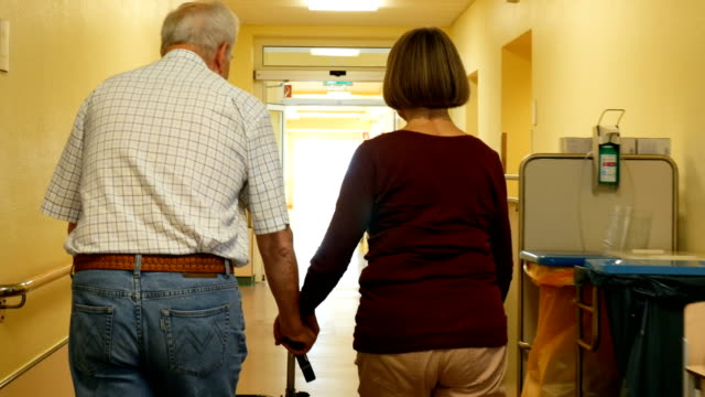 rear view of couple walking in corridor at clinic - wheelchair stock videos and b-roll footage