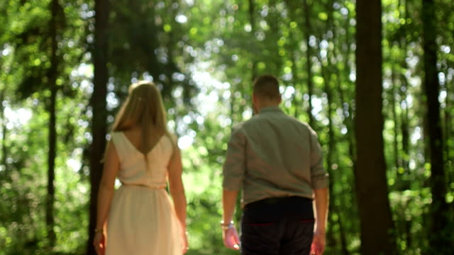 MEDIUM SHOT TRACKING SHOT Rear view of couple walking in forest on sunny day