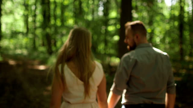 MEDIUM SHOT TRACKING SHOT TILT DOWN Rear view of couple walking in forest on sunny day