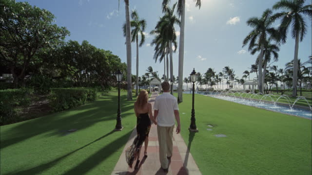 ws, ds, rear view of couple walking on footpath in luxurious resort, maui, hawaii, usa - maui stock videos & royalty-free footage