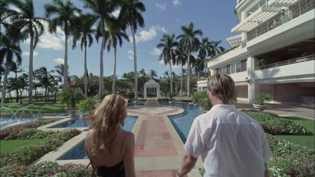 ws, ds, rear view of couple walking on footpath through swimming pool in luxurious resort, maui, hawaii, usa - fan palm tree stock videos & royalty-free footage
