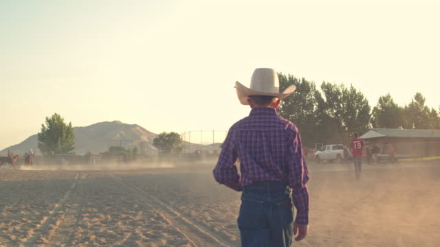Rear view of cowboy child walking in the arena, Utah, USA