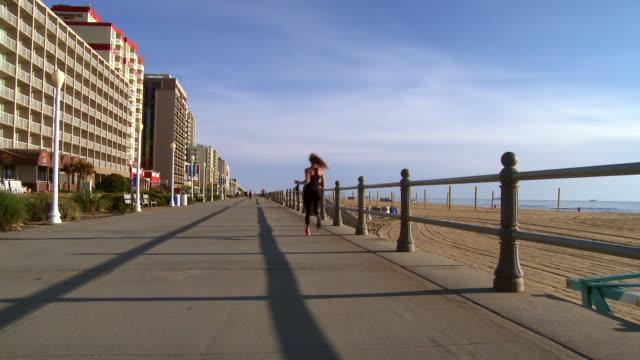 rear view of distant caucasian teenage girl running on boardwalk - virginia beach stock videos & royalty-free footage