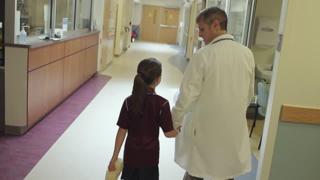 vídeos de stock, filmes e b-roll de ms tu td rear view of doctor and girl (8-9) holding teddy bear walking through hospital corridor / portland, maine, usa - vista traseira