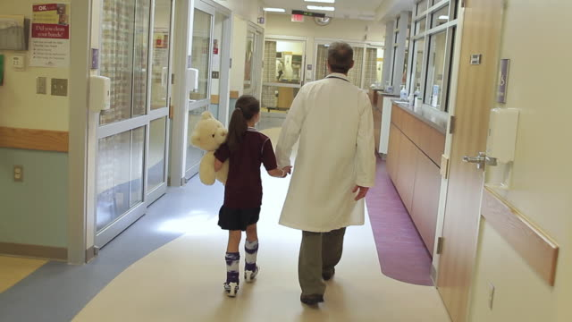 WS Rear view of doctor and girl (8-9) holding teddy bear walking through hospital corridor / Portland, Maine, USA