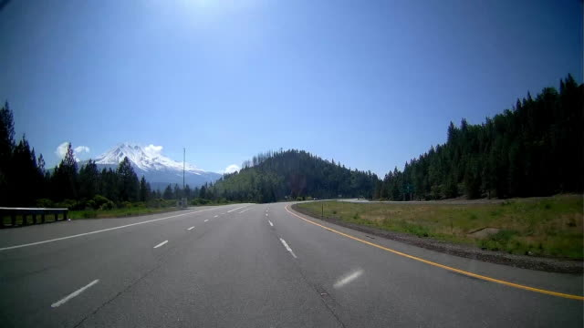 rear view of driving with snowcapped mountain in the background in alaska - distant stock videos and b-roll footage