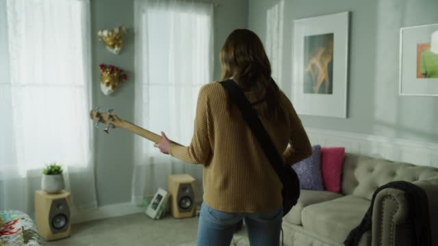 rear view of enthusiastic girl practicing playing guitar in livingroom / cedar hills, utah, united states - guitarist stock videos & royalty-free footage