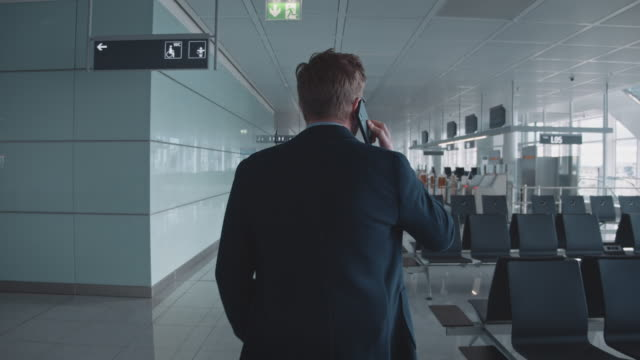 vídeos de stock e filmes b-roll de rear view of executive talking on phone in airport - vista traseira