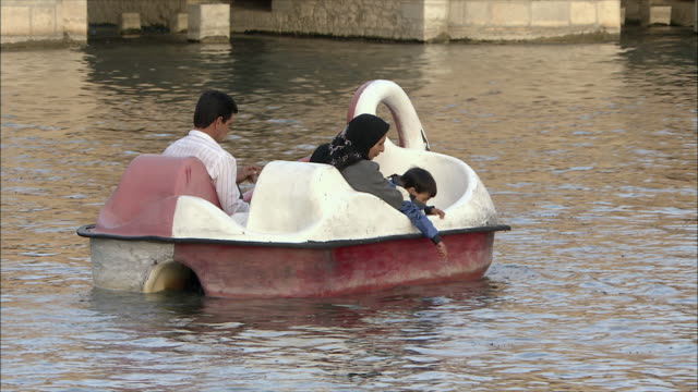 MS Rear view of family with boy in swan shaped pedalo on Zayandeh River, Khaju Bridge in background, Isfahan, Iran