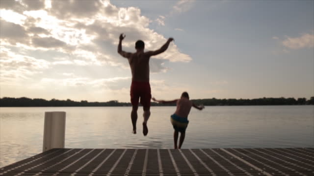 rear view of father and son jumping in lake during sunset - pier点の映像素材/bロール