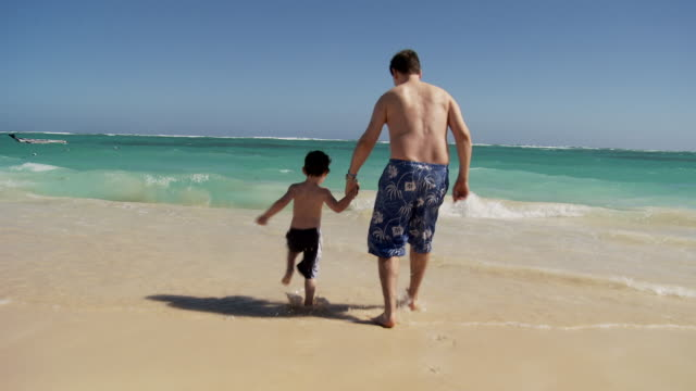 CU, WS, CS, Rear view of father and son (2-3) running into ocean waves, Punta Cana, Dominican Republic