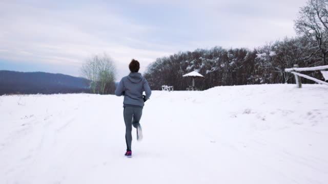 Rückansicht des weiblichen Athleten laufen auf dem Schnee in der Natur.