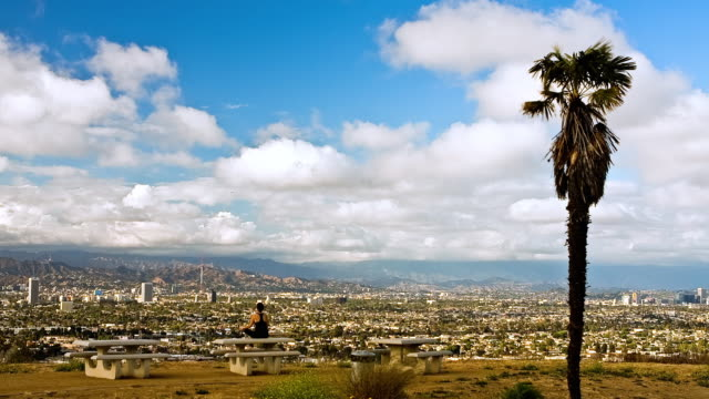 T/L WS Rear view of female jogger relaxing on picnic table at Baldwin Hills Park, cityscape and mountains in background, Los Angeles, California, USA
