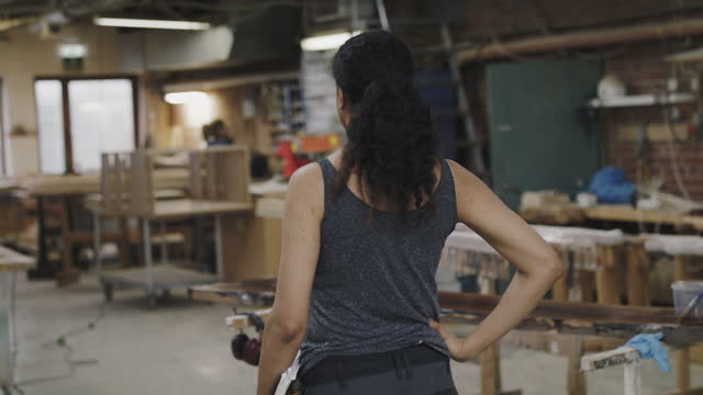 rear view of female owner standing with hand on hip looking around at workshop - hand on hip stock videos & royalty-free footage