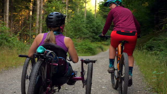 ts rear view of female wheelchair athlete and friend on mountain bike ride - persons with disabilities stock videos & royalty-free footage
