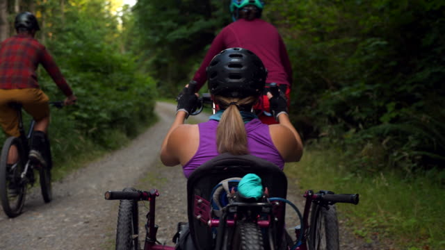 ms rear view of female wheelchair athlete and friends on mountain bike ride - mid adult women stock videos & royalty-free footage