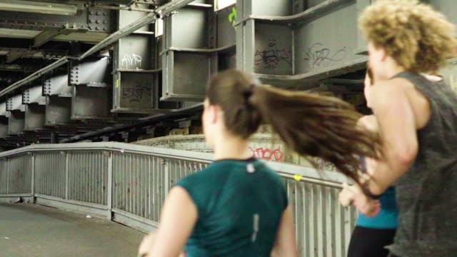 Rear view of friends jogging under metallic bridge